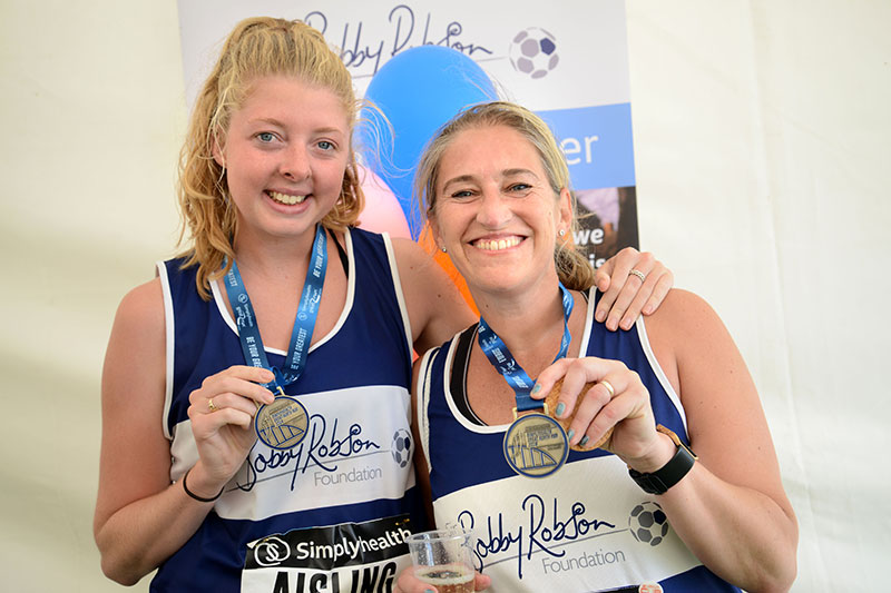 Two women with GNR medals in the Sir Bobby Robson Foundation tent